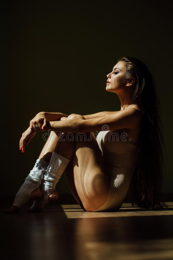 Beautiful modern ballet dancer with perfect body sits on the floor in the studio hall. royalty free stock photos