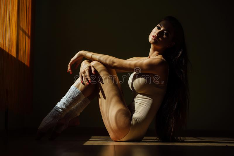 Beautiful modern ballet dancer with perfect body sits on the floor in the studio hall. royalty free stock photography
