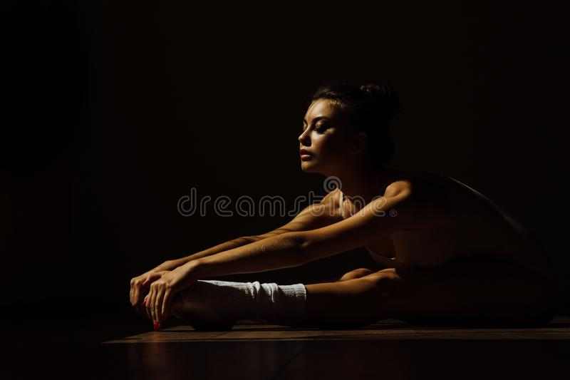 Beautiful modern ballet dancer with perfect body sits on the floor in the studio hall. stock photos
