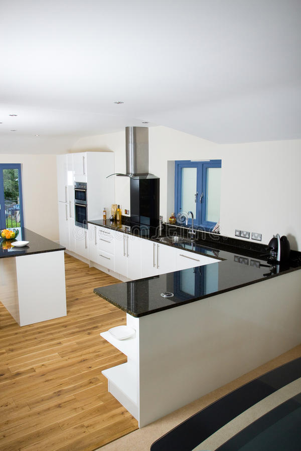 Beautiful modern kitchen. An brand new open plan kitchen and dining area in a large contemporary property royalty free stock photography