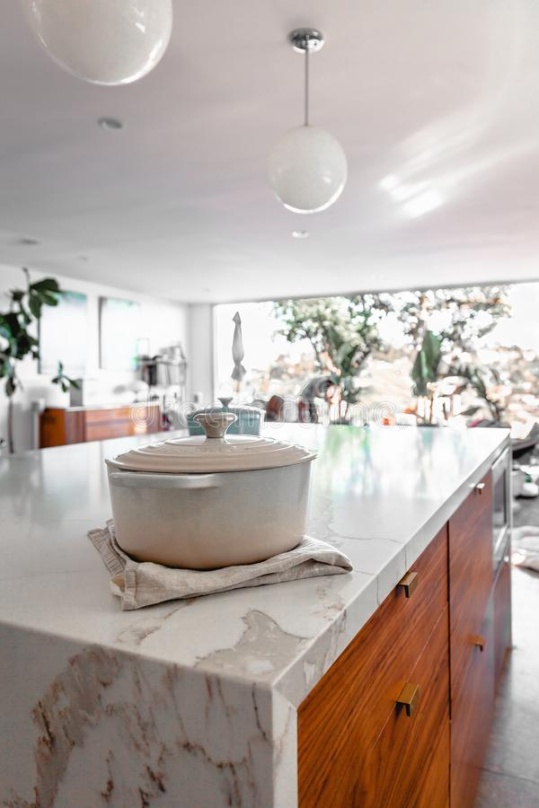 Beautiful modern kitchen interior with a white metal pot on the table stock photography