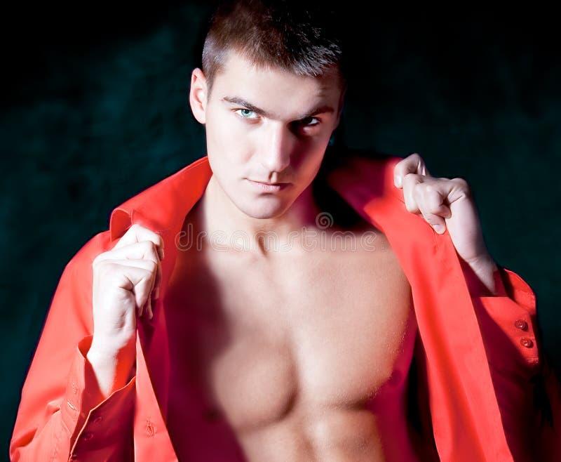 Beautiful modern macho man in red shirt  is posing