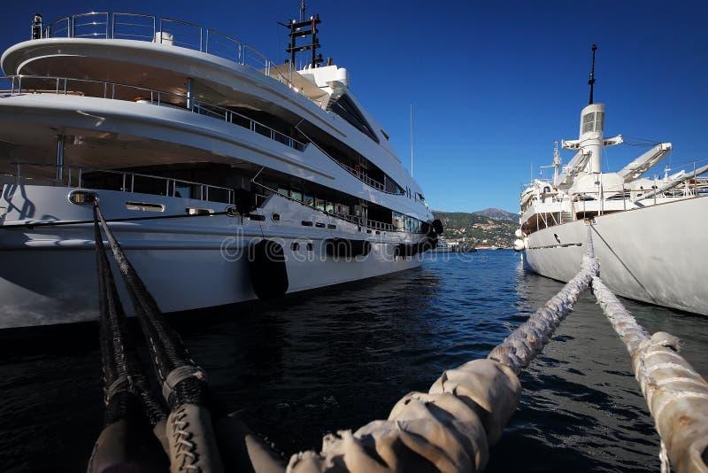Beautiful modern ships at moorage. Photo closeup of beautiful modern white ships sea liners yachts vessels at moorage with nautical ropes at seashore clear water stock image