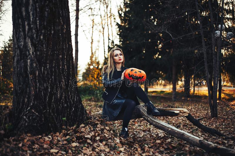 Beautiful modern witch holding halloween pumpkin in the forest. october. happy holidays stock photo