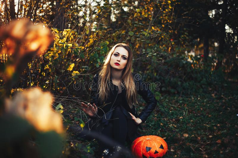 Beautiful modern witch holding halloween pumpkin in the forest. october. happy holidays.  royalty free stock photos