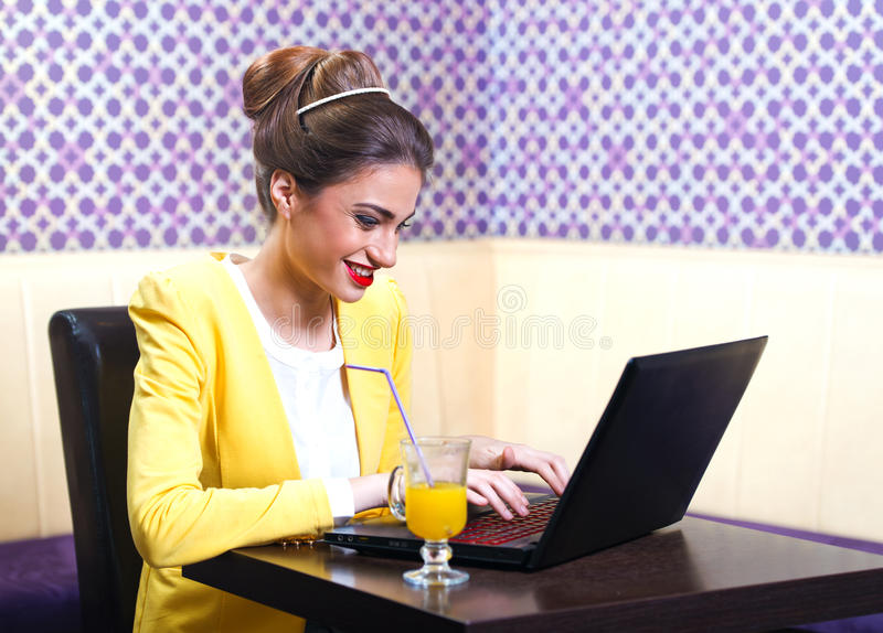Beautiful modern young woman sitting at the laptop royalty free stock image