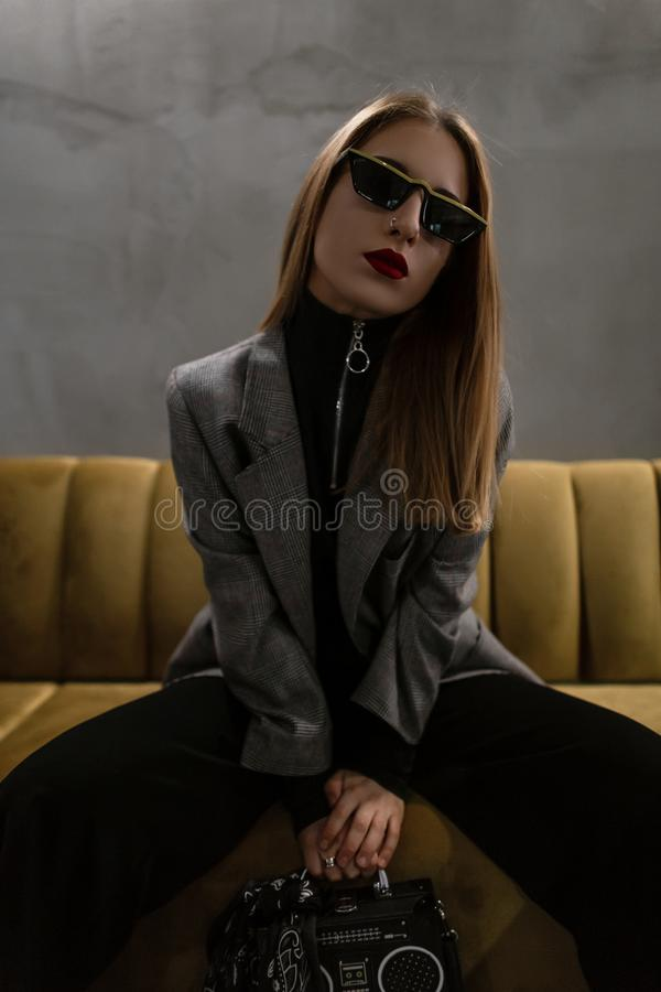 Beautiful modern young women hipster with pierced nose with red lips in a vintage gray checkered jacket in black pants stock image
