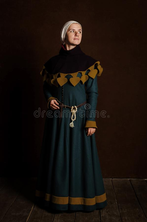 Beautiful modest girl in a medieval dress with a hood royalty free stock photography