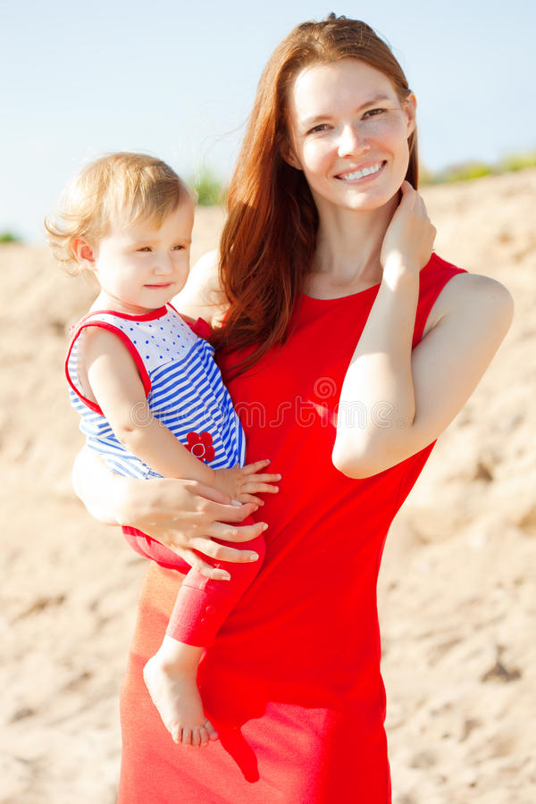 Beautiful Mom and baby outdoors. Happy family playing on the beach. Mom and baby. Mother and child. stock image
