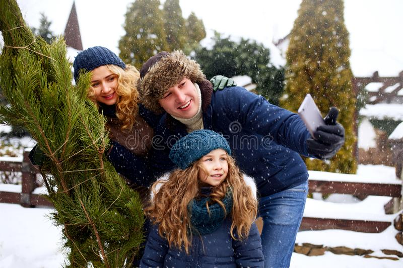 Beautiful mom, dad and daughter doing selfie with freshly cut christmas tree with smartphone near home. Young family stock photography