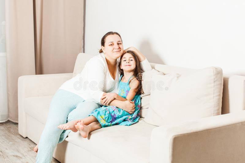 Beautiful mom and daughter in the living room. stock photography