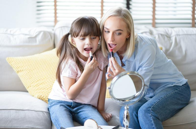 Beautiful mom with her little cute daughter are doing your makeup and having fun. Mom and daughter wear lipstick look at mirror royalty free stock image
