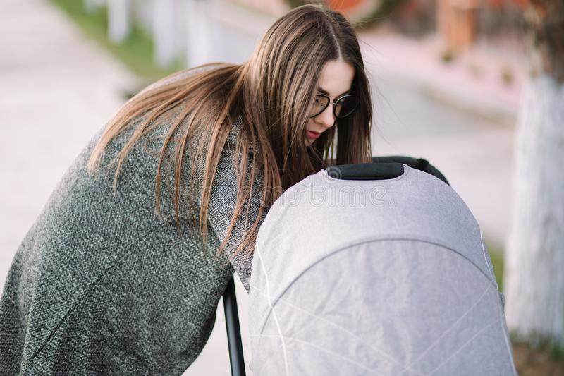 Beautiful mom look in to the stroller. Young mother walking with baby. Happy family stock images