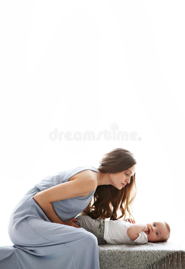 Beautiful mom looking at her sweet baby. Fashion model in long blue dress gently with love hugging her son stock photography
