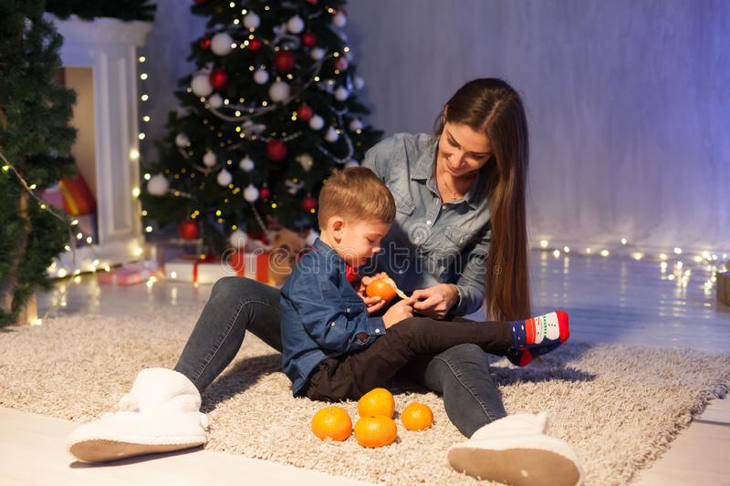 Beautiful mom with son at christmas tree with new year decor gifts royalty free stock image