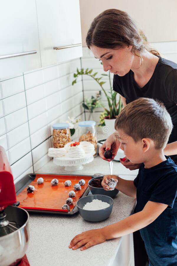 Beautiful woman mom and son together cooks sweet cakes in the kitchen royalty free stock photography