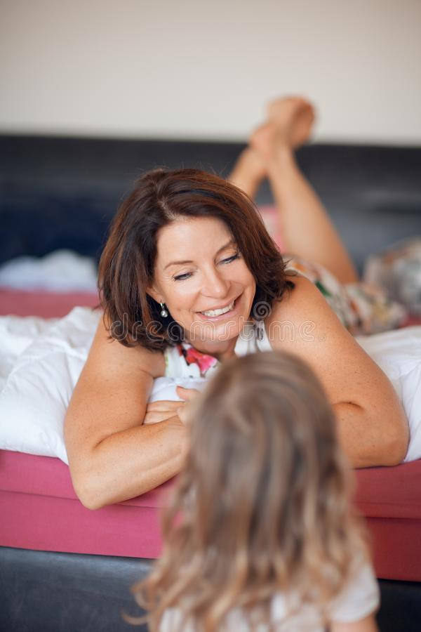 Beautiful mom talks to her little daughter. Lying in bed at home royalty free stock images