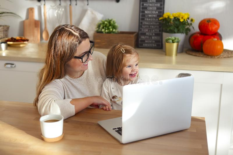 Beautiful mom working at home on a laptop computer while taking care of her baby girl stock photography
