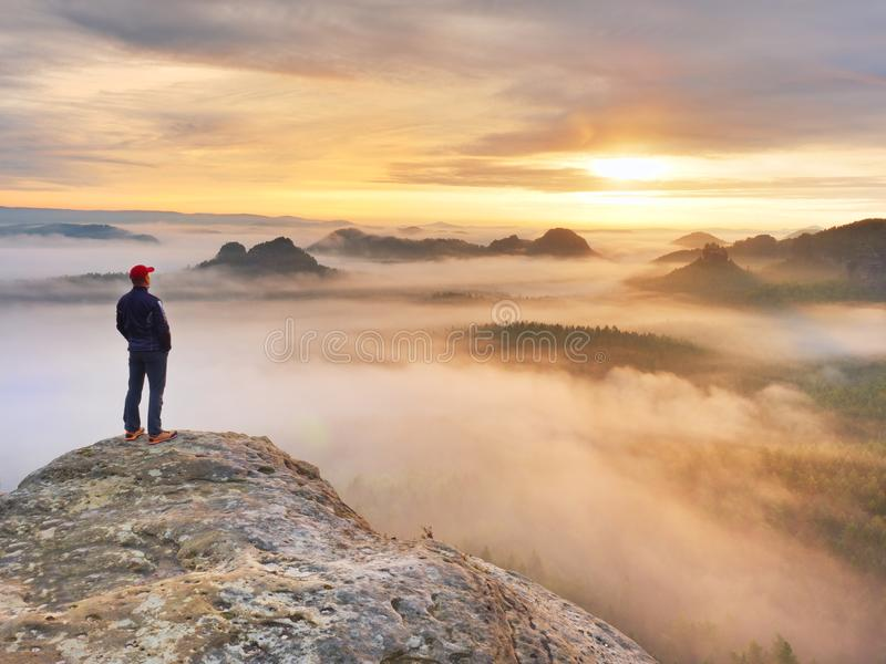 Beautiful moment the miracle of nature. Colorful mist in valley. Man hike. Person silhouette stand. Man stands alone on the peak of rock. Hiker watching to royalty free stock photography