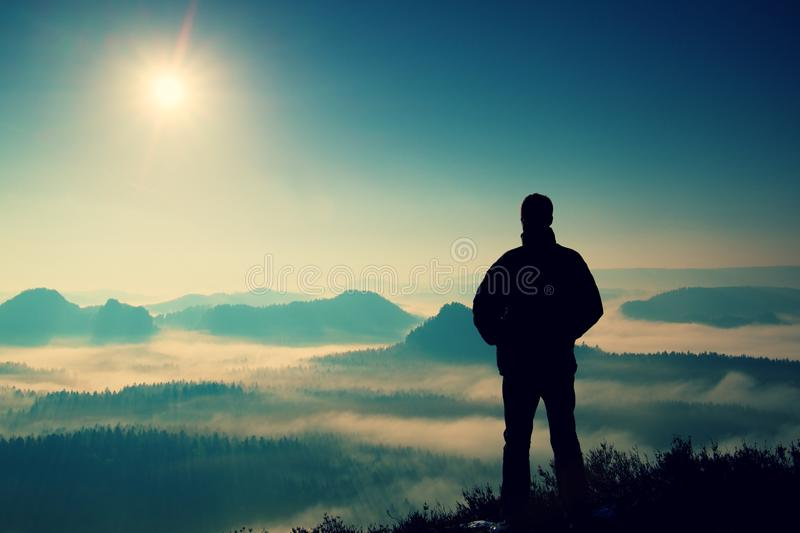 Beautiful moment the miracle of nature. Man stands on the peak of sandstone rock in national park Saxony Switzerland and watching. Man stands on the peak of stock photography