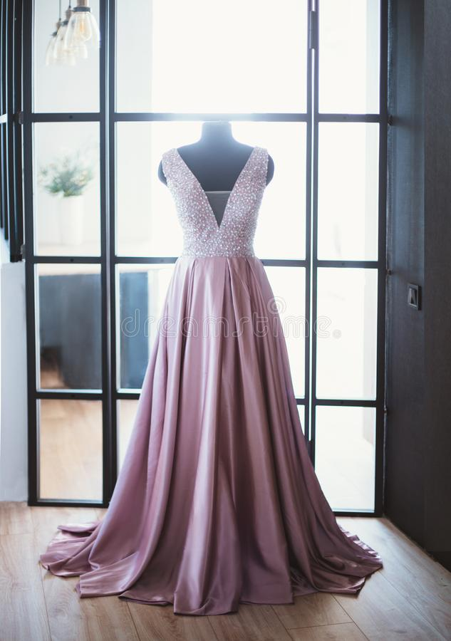 Beautiful monophonic satin silk pink purple purple long cute dress with a deep neckline for the princess, put on a royalty free stock photography