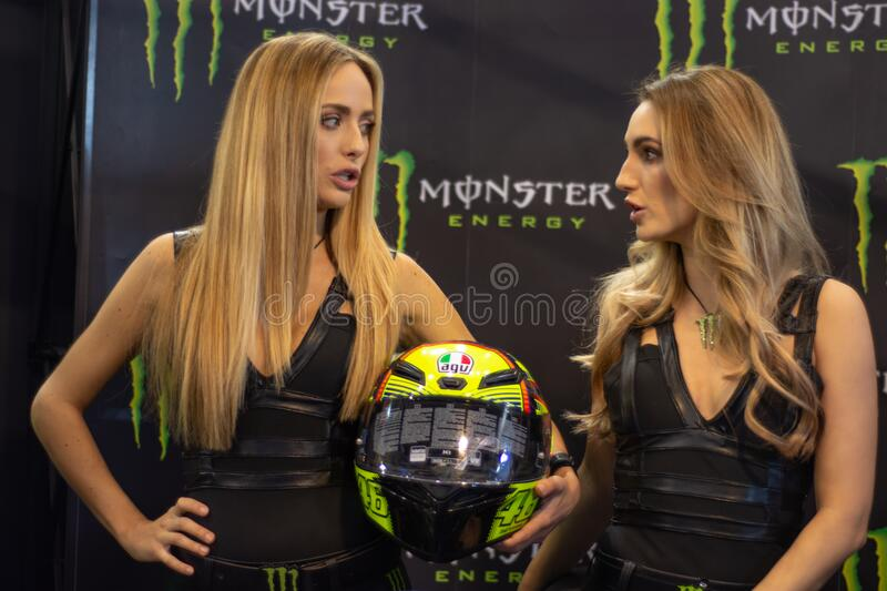 Beautiful Monster Energy girls pose with the motorcycle at Belgrade Car and Motor Show. Belgrade / Serbia - March 30, 2019: Beautiful Monster Energy girls pose stock photos
