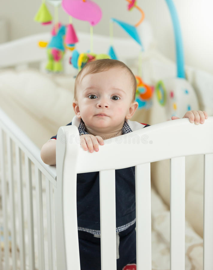 Beautiful 9 months old baby boy standing in crib at bedroom royalty free stock photography