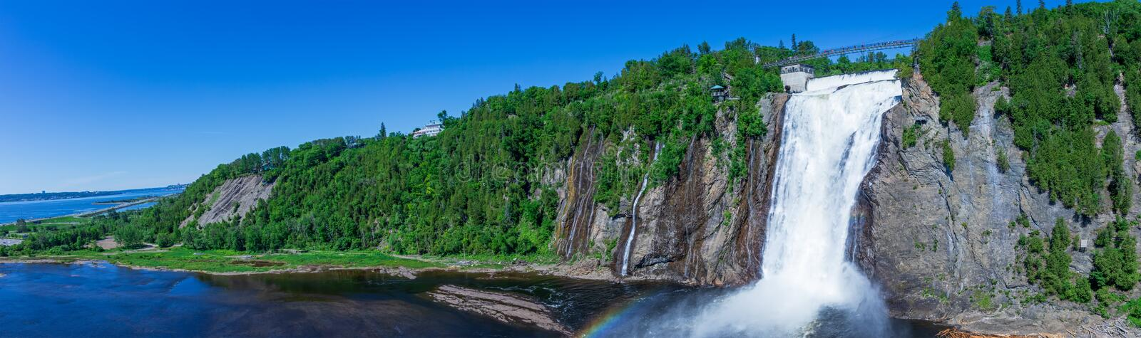 Beautiful Montmorency Falls with rainbow and blue sky. View of Canadian fall located near Quebec City, Canada in North America stock photography