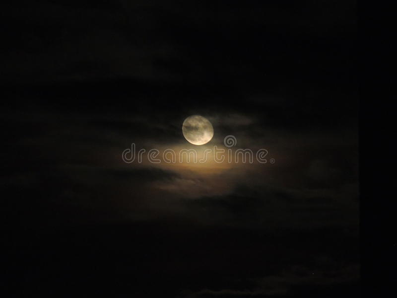 Beautiful moon. Beautiful full moon shinning bright with hovering clouds , a bit yellowish stock photo
