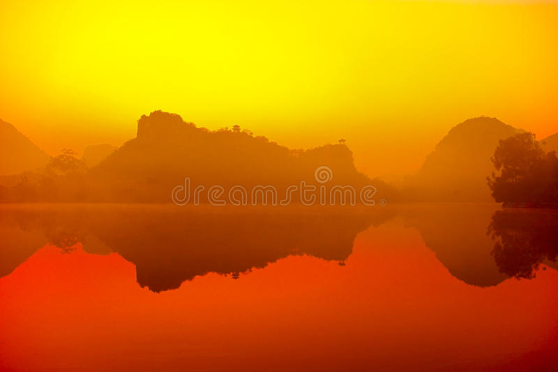 Beautiful morning. The early morning mist hanging over the lake, mountain reflection in the water stock image
