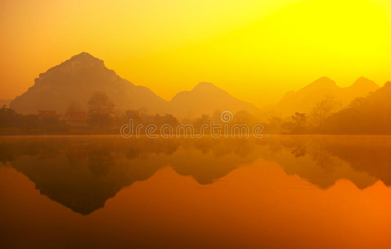 Beautiful morning. The early morning mist hanging over the lake, mountain reflection in the water stock photography