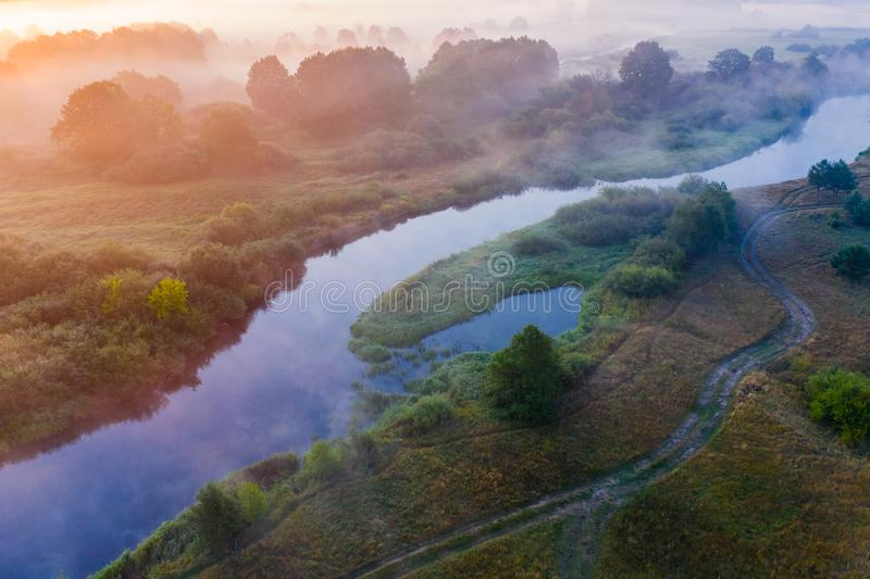 Beautiful morning. Fog concept. Bright sunrise. River flows along misty rural area royalty free stock photo
