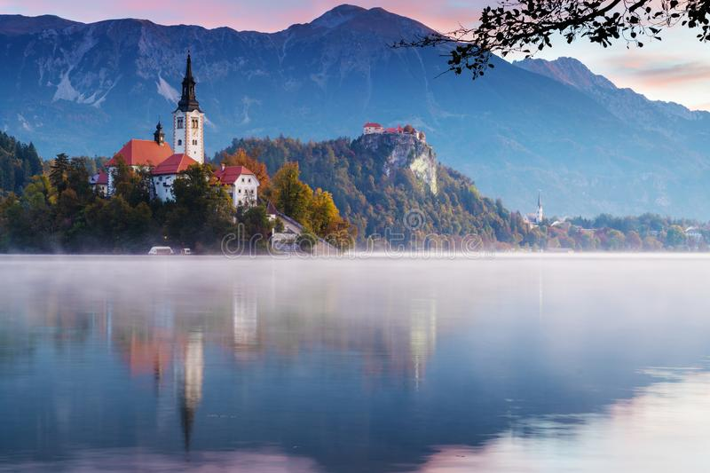 Morning at lake Bled. Church on island with castle and mountains in background. Beautiful morning at lake Bled during sunrise. Mist lingering over the lake with stock photos