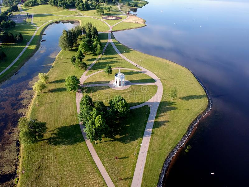 Lake coast in city park with paths and meadow, aerial view. Beautiful morning lake coast in city park with paths and meadow, aerial view royalty free stock images
