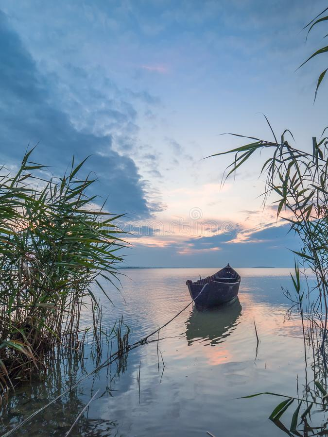 Beautiful morning landscape with a boat on the lake at the sunrise through the reed royalty free stock photos