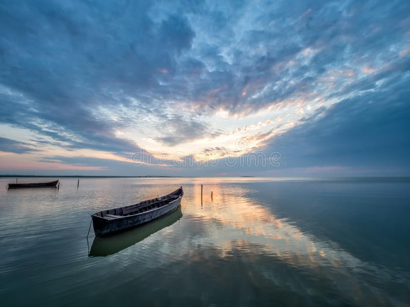 Beautiful morning landscape with boats on the lake at the sunrise royalty free stock photography