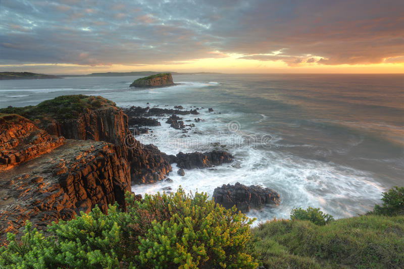 Beautiful morning with soft light on the rocks at Minamurra. Magnificent sunrise morning and beautiful soft sunlight highlighting the rocks at Minamurra stock images