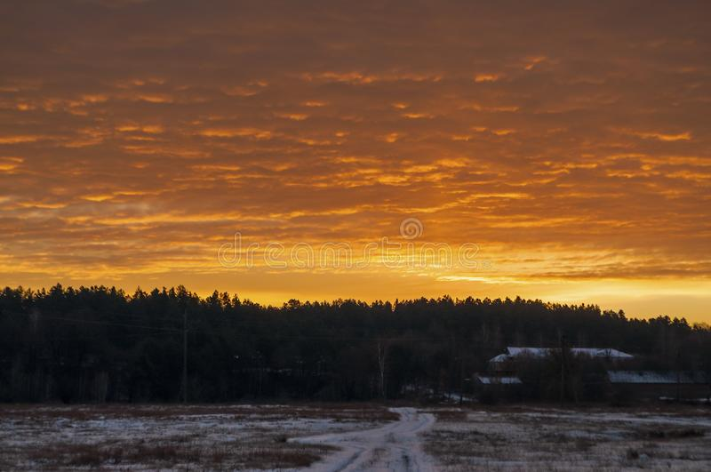 Beautiful morning and winter bright sunrise in January. Suburb and field covered snow royalty free stock photography