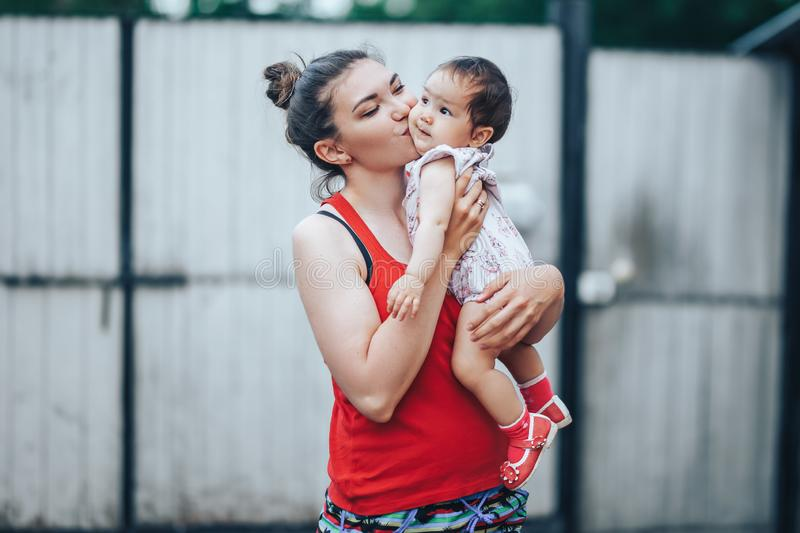 Beautiful Mother And Baby outdoors on the yard of house. Beauty Mum and her baby Child one year old playing in yard together. Mom. And Baby royalty free stock photography