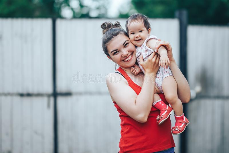 Beautiful Mother And Baby outdoors on the yard of house. Beauty Mum and her baby Child one year old playing in yard together. Mom. And Baby stock image