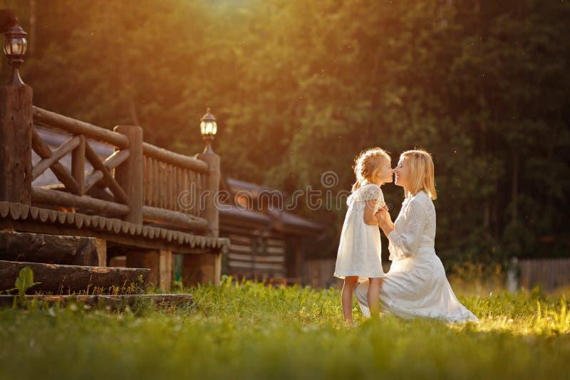 Beautiful mother blonde in white dress gently hugs a girl kneeli stock photo