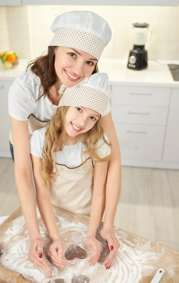 Mother and daughter posing, making heart shaped cookies. royalty free stock image