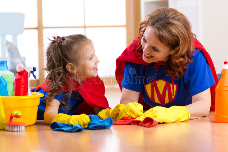 Beautiful mother and cute kid daughter dressed like superheroes. Woman and child ready to cleaning the house. stock image
