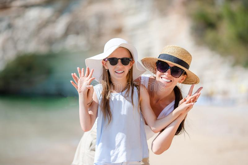 Beautiful mother and daughter at the beach enjoying summer vacation. stock image