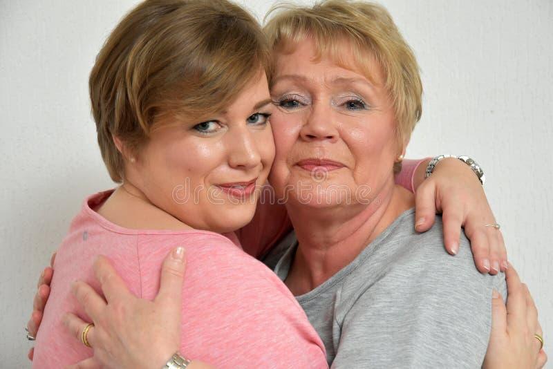 Beautiful mother and daughter. Close-up portrait of a beautiful mother and daughter smiling at the camera stock image