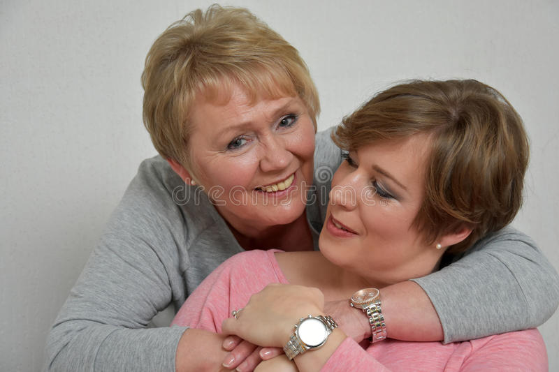 Beautiful mother and daughter. Close-up portrait of a beautiful mother and daughter smiling at the camera royalty free stock images