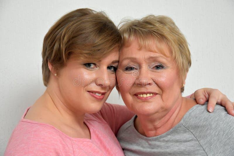 Beautiful mother and daughter. Close-up portrait of a beautiful mother and daughter smiling at the camera stock photo