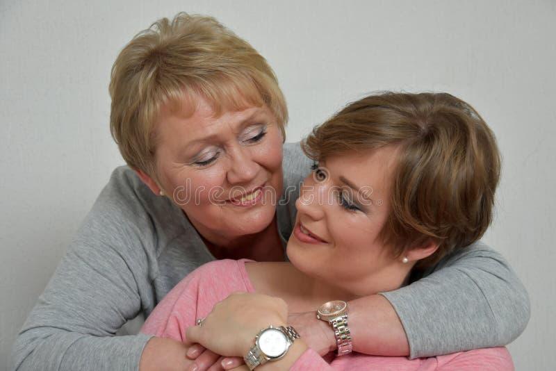 Beautiful mother and daughter. Close-up portrait of a beautiful mother and daughter smiling at the camera stock photos