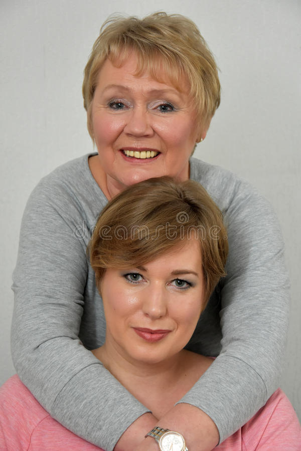 Beautiful mother and daughter. Close-up portrait of a beautiful mother and daughter smiling at the camera royalty free stock photography