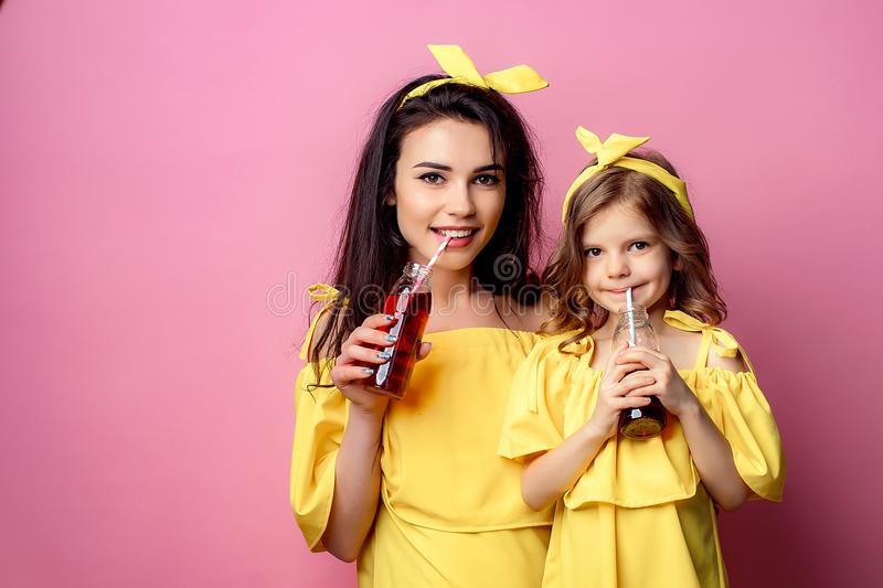 Beautiful mother with daughter drinking through straw stock image